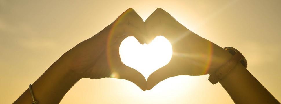 cuore con le mani al tramonto